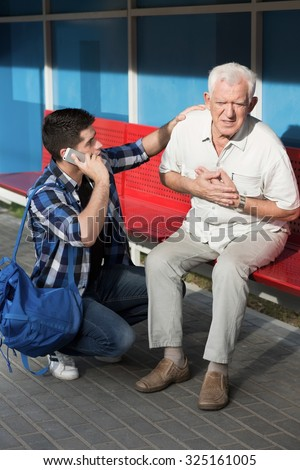Ill man and helper calling for emergency service - stock photo