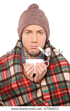 Ill man covered with blanket holding a tea cup and thermometer in his mouth isolated on white background