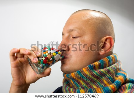 Ill man drinking cocktail of colorful pills - stock photo