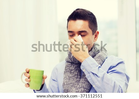 ill man with flu drinking tea and blowing nose - stock photo