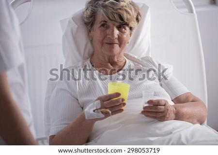 Ill older woman at hospital taking pills - stock photo