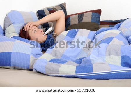 ill person with fever thermometer  lying in bed - stock photo