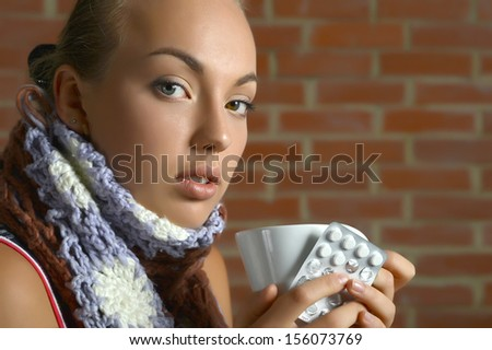Ill pretty young girl taking pills on brick wall background - stock photo