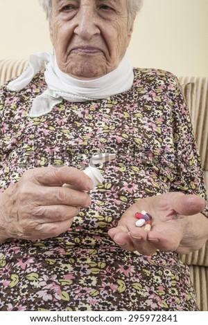 ill senior person taking pills - stock photo
