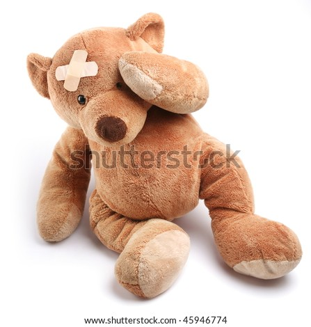 Ill teddy bear with plaster on its head. Isolated on a white background. - stock photo