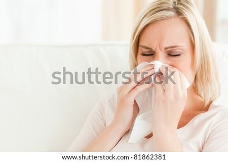Ill woman blowing her nose in her living room