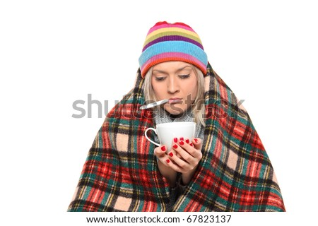 Ill woman covered with blanket holding a tea cup and a thermometer in her mouth isolated on white background - stock photo