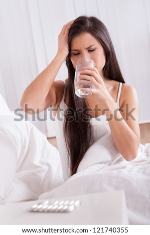 Ill woman in bed taking medication sitting up holding a glass of water looking at a tablet in her hand