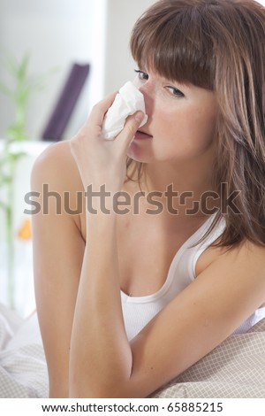 ill woman in bed with handkerchief sneezing