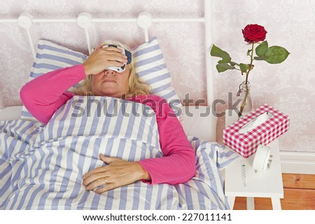 Ill woman in pink pajama with headache, tissues and a rose lying in bed with washcloth - stock photo