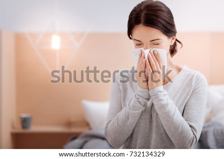 Ill woman sitting at home and sneezing