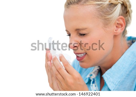 Ill woman sneezing into tissue on white background