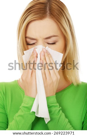 Ill woman sneezing to tissue. - stock photo