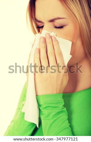 Ill woman sneezing to tissue. - stock photo