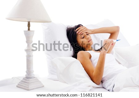 ill woman taking her temperature in bed wile feeling sick and with fever - stock photo