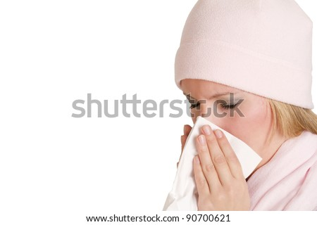 Ill Woman With Flu Sneezing, Woman dressed in winter clothing holding a tissue to her nose in a cold and flu health concept.