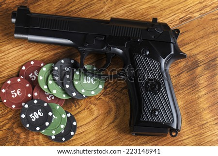 Illegal gambling concept handgun with betting chips - stock photo