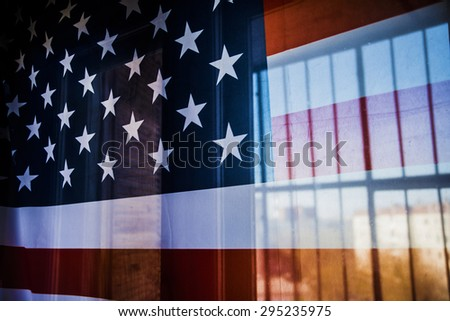 Illegal immigration concept Background of transparent American flag behind a chain link fence and houses outdoor behind glass window Empty space for inscription  - stock photo