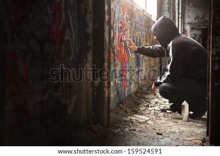 Illegal Young man Spraying black paint on a Graffiti wall. (room for text) - stock photo