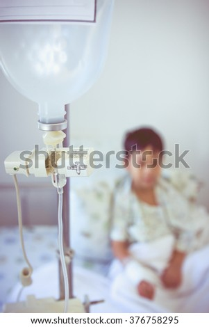 Illness asian boy sitting on sickbed in hospital with infusion pump intravenous IV drip. Shallow depth of field (DOF) drop in intravenous (IV) drip in focus, child out of focus. Retro style. - stock photo