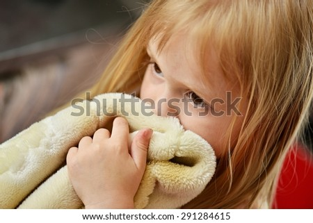 Illness child. Little girl wrapped in a blanket - stock photo