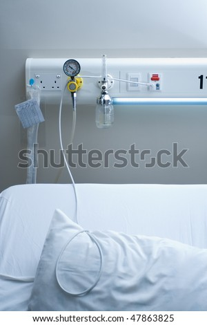 illness concept image of bed with emergency health equipment panel above - stock photo