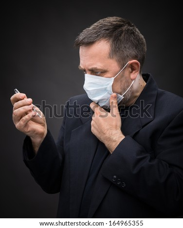 Illness. Man in medical mask with a thermometer - stock photo
