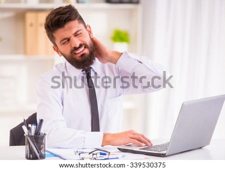Illness neck. Portrait of a businessman with a beard while working in his office, holding his neck