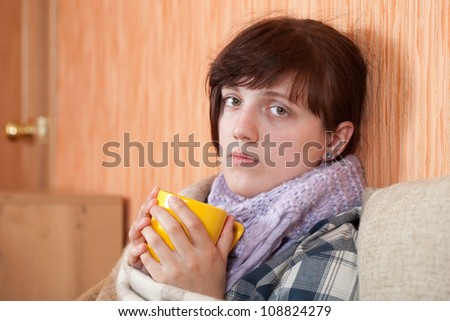 illness woman in warm scarf with hot cup