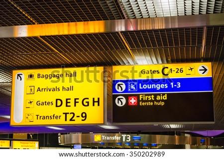 Illuminated airport departure gates direction sign - stock photo