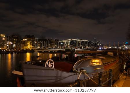 illuminated amsterdam canal and drawbridge at night - stock photo