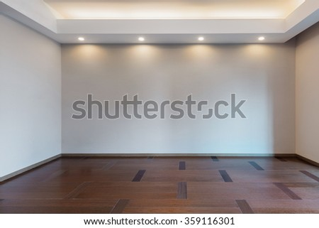 Illuminated and empty living room in grey color