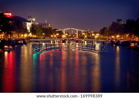 Illuminated and reflected bascule Magere Brug Bridge on Amstel river of Amsterdam, with light trails of boats passing on the water. - stock photo