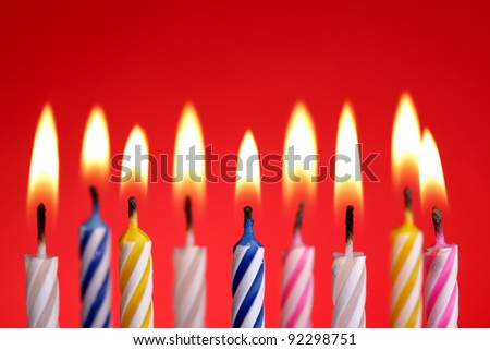 Illuminated birthday candles on red background - stock photo