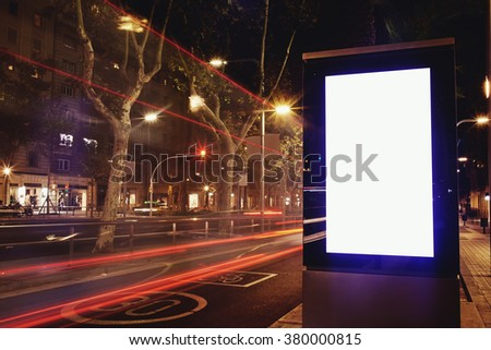 Illuminated blank billboard with copy space for text message or promotional content, public information board in night city with cars light on background, advertising mock up banner in urban scene  - stock photo
