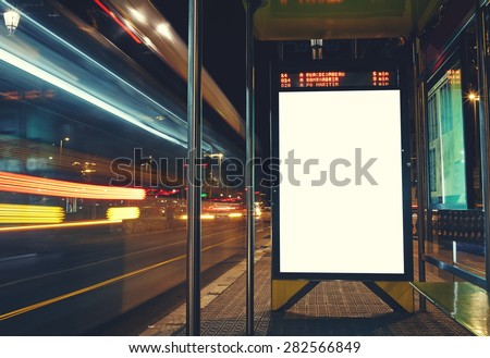 Illuminated blank billboard with copy space for your text message or content, advertising mock up banner of bus station, public information board with blurred vehicles in high speed in night city  - stock photo