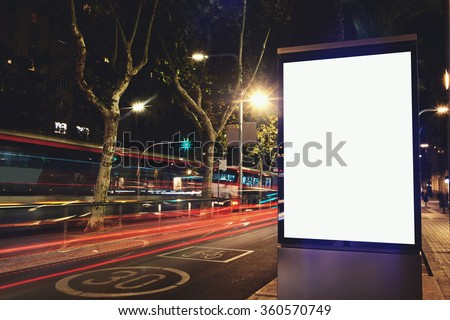 Illuminated blank billboard with copy space for your text message or content, public information board in night city with movement of car on background, advertising mock up banner in urban setting - stock photo