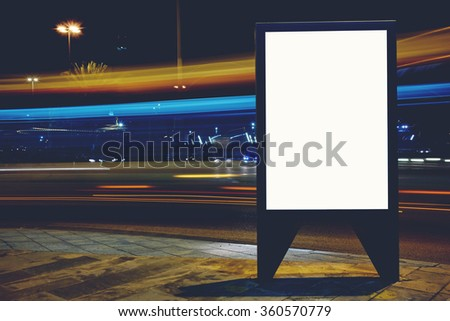 Illuminated blank billboard with copy space for your text message or promotional content, advertising mock up banner on roadside in night, public information board with blurred vehicles on high speed - stock photo