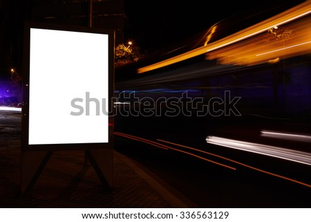 Illuminated blank billboard with copy space for your text message or promotional content, public information board in city with night light on background, advertising mock up banner on roadway  - stock photo