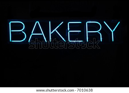 Illuminated blue bakery neon sign on a black background