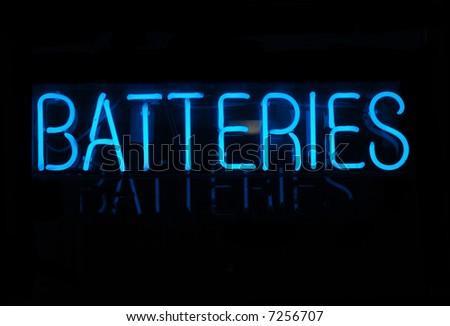 Illuminated blue batteries neon sign on black - stock photo