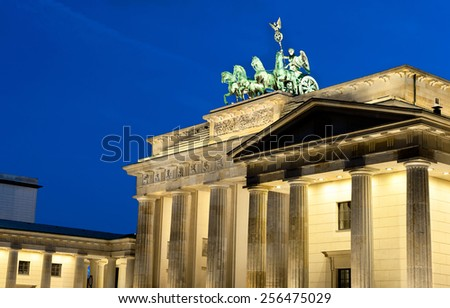 Illuminated Brandenburg Gate in Berlin, Germany, with famous quadriga on top. Focus on the gate top and the quadriga.