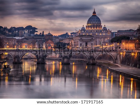 Illuminated bridge in Rome, Italy. Saint Peters basilica in the background. - stock photo
