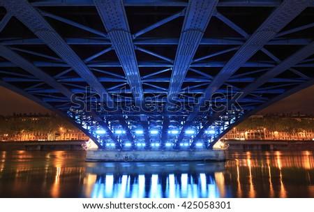 Illuminated bridge over the Rhone river in Lyon at dusk. - stock photo