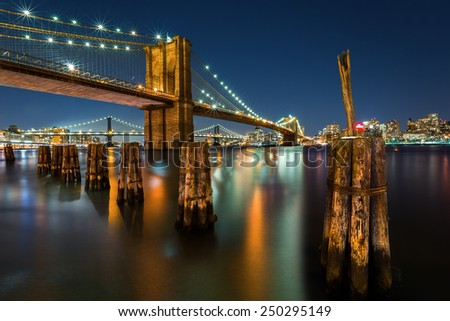 Illuminated Brooklyn Bridge by night as viewed from the Manhattan side. - stock photo