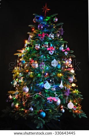 illuminated Christmas tree on dark background - stock photo