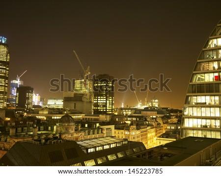 Illuminated cityscape with cranes at night - stock photo