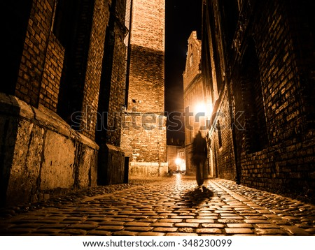 Illuminated cobbled street with light reflections on cobblestones in old historical city by night. Dark blurred silhouette of person evokes Jack the Ripper. - stock photo