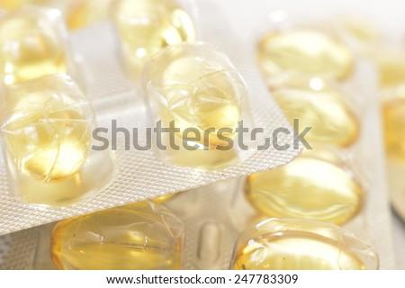 illuminated cod-liver  yellow transparent pills - stock photo