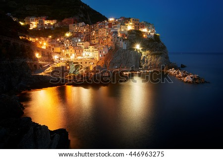Illuminated, colorful village Manarola, famous world heritage italian site in evening, mirroring lights in the sea, deep blue sky,colorful houses,  dramatic coastal scenery. Cinque terre, Italy. - stock photo